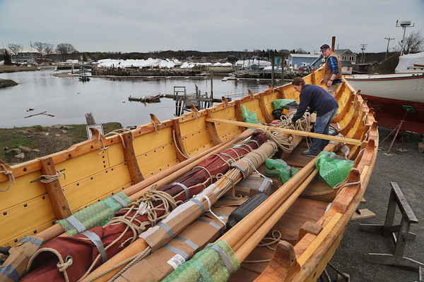 MIKE SPRINGER/Staff photo<br /> Stuart Boyd of Beverly and Karen Angelli of Hamilton unpack various components -- oars, mast, sail and rigging -- from the Viking-style boat Polaris on Friday at the Essex Shipbuilding Museum.<br /> 4/27/2018