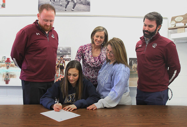 MIKE SPRINGER/Staff photo<br /> Gloucester High School track athlete Kaitlin Marques signs a letter of intent Wednesday to attend Merrimack College next year. Standing around her are, from left, GHS head track coach Dave Coleman, athletic director Julie Smith, Kaitlin's mother Maria Nunes, and assistant track coach Jeff Destino.<br /> 4/11/2018