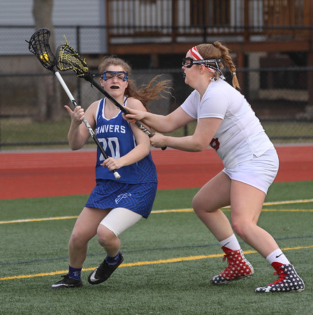 MIKE SPRINGER/Staff photo<br /> Natalie Gesualdi, left, of Danvers is pursued by Gloucester's Ruby Melvin during lacrosse action Friday in Gloucester.<br /> 4/13/2018