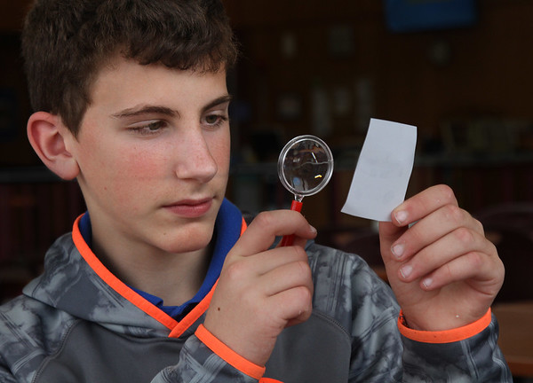 "MIKE SPRINGER/Staff photo<br /> Eighth-grader Peter Scola uses a magnifying glass to study a fingerprint during a meeting Wednesday of the after-school ""Master Detectives"" club at O'Maley Innovation Middle School in Gloucester. The club, which meets once a week, is led by guidance counselor Paula Gray, a fan of the Sherlock Holmes mystery series. Each week the students are given a different scenario and an assortment of clues, such as fingerprints, footprints, handwriting and various substances that can be analyzed chemically. When the mystery is solved, the students get to watch a different Sherlock Holmes movie every week.<br /> 4/25/2018"