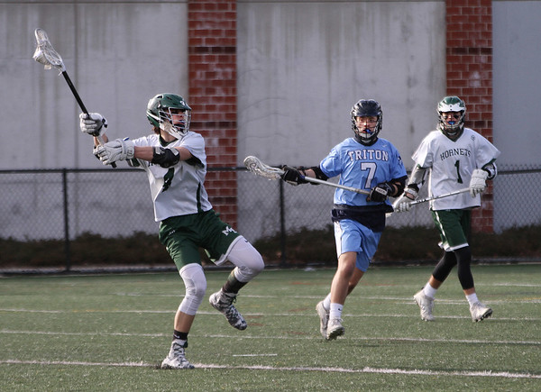 MIKE SPRINGER/Springer<br /> Jake Athanas, left, of Manchester Essex prepares to take a shot as Triton's Peter Drew and the Hornets' Clayton Boom look on during varsity lacrosse play Tuesday in Manchester.<br /> 4/24/2018