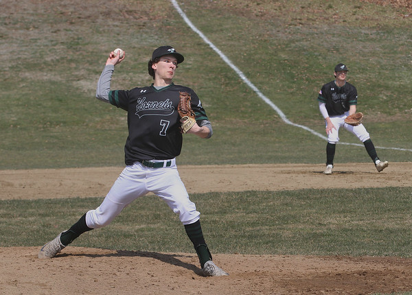 MIKE SPRINGER/Staff photo<br /> Will Janowicz pitches for Manchester Essex as first baseman Jackson Levendusky stands ready during varsity baseball action Saturday in Rockport.<br /> 4/14/2018