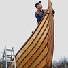 MIKE SPRINGER/Staff photo<br /> Stuart Boyd of Beverly examines the bow stem of the Polaris, a 37-foot reproduction of a traditional viking boat, on Friday at the Essex Shipbuilding Museum. Boyd commissioned the boat from a custom builder of Nordic boats in Anacortes, Washington. The design is modeled on a 1,000-year-old boat on display in Denmark.<br /> 4/27/2018
