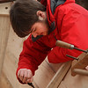 MIKE SPRINGER/Staff photo<br /> Ryan Bashaw of Newbury, a sophomore at the Topsfield Vocational Academy, uses a chisel to cut a recess in the frame of a 20-foot Banks dory on Thursday in Essex.<br /> 4/12/2018