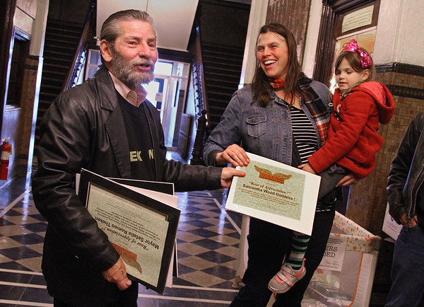 MIKE SPRINGER/Staff photo<br /> Event organizer Paul Cote of Amesbury presents Samantha Wood Goddess of Gloucester, holding her five-year-old daughter Francesca, with a surprise certificate of appreciation for her help in promoting motorcycle safety during a ceremony Wednesday in the rotunda of Gloucester City Hall. Goddess was one of three people honored during the event, which also included a proclamation from Mayor Sefatia Romeo Theken.<br /> 4/25/2018