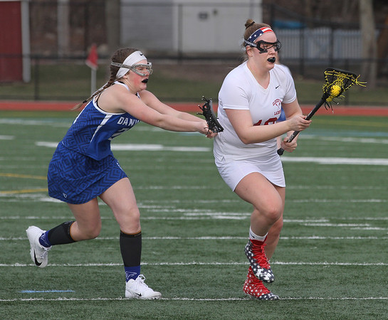 MIKE SPRINGER/Staff photo<br /> Gloucester's Ruby Melvin, right, brings the ball upfield under defensive pressure from Emma Thibodeau of Danvers during lacrosse action Friday in Gloucester.<br /> 4/13/2018
