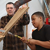 MIKE SPRINGER/Staff photo<br /> Volunteer Tom Ash, a firefighter from Topsfield, holds the wood steady as Raymond Dancy of Salem, a freshman at the Northshore Education Consortium's Topsfield Vocational Academy, uses a saw to cut the outline of the transom of a 20-foot Banks dory Thursday at the Essex Shipbuilding Museum.<br /> 4/12/2018