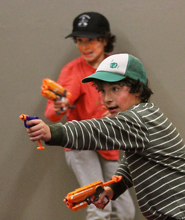 "MIKE SPRINGER/Staff photo<br /> Ten-year-old Solomon Rich, right, and his twin brother Winston take aim Monday during a special vacation-week ""Nerf Battle"" at the Cape Ann YMCA in Gloucester.<br /> 4/16/2018"