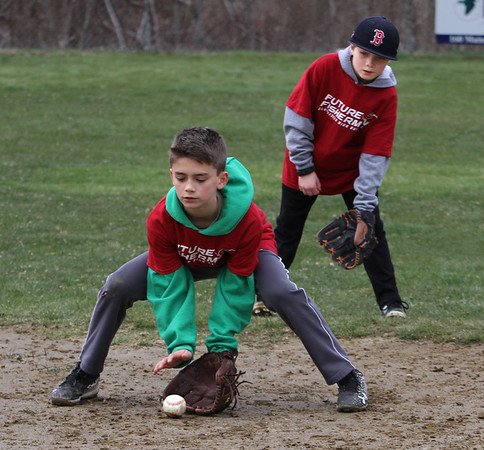 MIKE SPRINGER/Staff photo<br /> Ten-year-old James Cook fields the bll as Gabe Anderson, 9, looks on Tuesday during the annual Future Fishermen Little League Clinic in Gloucester.<br /> 04/17/2018