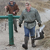 MIKE SPRINGER/Staff photo<br /> Erik Amati, a wildlife biologist with the Massachusetts Division of Fisheries and Wildlife, carries a dead seagull from Good Harbor Beach in Gloucester after he and Mass Wildlife technition Josh Gahagan, left, found it Tuesday while investigating the presence of piping plovers on the beach. The dead gull had a metal band around its leg, indicating that it was part of a federal research project.<br /> 4/10/2018