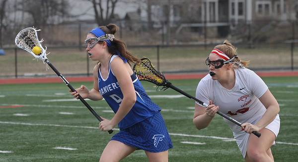 MIKE SPRINGER/Staff photo<br /> Ashley Curcuru, left, of Danvers carries the ball upfield under defensive pressure from Gloucester's Ruby Melvin during lacrosse action Friday in Gloucester.<br /> 4/13/2018