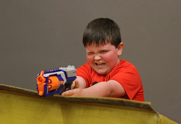 "MIKE SPRINGER/Staff photo<br /> Eight-year-old Keagan Poole takes aim during a ""Nerf Battle"" with other children Monday in the gymastics room of the Cape Ann YMCA in Gloucester. The battle was one of a series of special April vacation week events scheduled for this week at the YMCA.<br /> 4/16/2018"
