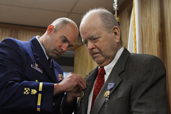 MIKE SPRINGER/Staff photo<br /> Ninety-three-year-old Robert Henry Leet of Ipswich stands still while Kevin Morgan, Commanding Officer of U.S. Coast Guard Station Gloucester, pins a medal on his lapel during a ceremony Friday at the station. Leet was awarded the World War II Victory Medal and the American Campaign Medal for his service in the Coast Guard Auxiiary during World War II, when he once spotted a German submarine off Crane Beach.<br /> 4/20/2018