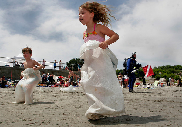 Rockport: Jackie Keenan, 5, of Rockport makes her way to the finish line during the potato sack race during the Old Garden Beach picnic Saturday afternoon. The picnic provided children with a variety of games including three-legged races, swimming races, and a spoon race.   <br /> Photo by Mary Muckenhoupt/Gloucester Daily Times. Saturday, July 15, 2006