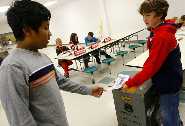"""Rockport: Ryan Balzarini, left, hands his ballot to Nate Young during Rockport Elementary School's """"Mock Election"""" on Wednesday. Young checked to make sure voters had checked in and out, but really liked making the box ding every time he collected a ballot. Photo by Kate Glass/Gloucester Daily Times Wednesday, October 29, 2008"""