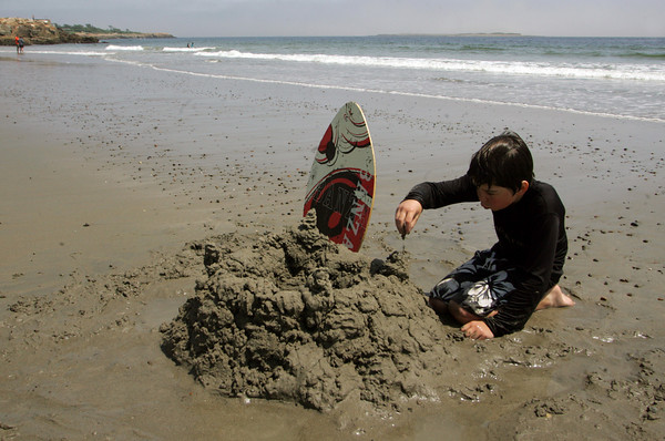 Rockport: Nicolas Thirion, 10, works on a drip castle by the water's edge at Cape Hedge Beach Friday. Nicolas and his family were happy to finally get out and enjoy the sunshine even though fog kept rolling in. Mary Muckenhoupt/Gloucester Daily Times