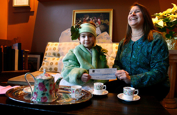 Essex: Samantha Turner, dressed as a fairy, hands a check for $1,000 to Michelle Baer of Cape Ann Habitat for Humanity from Underwood Photography in Essex. Tom Underwood and his wife, Jacqueline, donated proceeds from their 5th Annual Fairy Fest to the organization. Grace Kelly and Nicole Lucido from Gloucester High School, volunteered at the event and donated their wages to the organization as well. Photo by Kate Glass/Gloucester Daily Times Tuesday, December 23, 2008