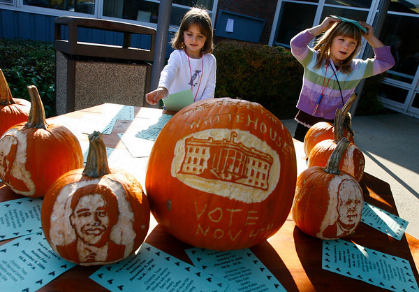 Gloucester: Ellie Sutera, 4, and Kate Bevins, 6, place fliers for the Beeman School's Holiday Fair around pumpkins carved with images of the Presidential candidates yesterday. The pumpkins were dropped off at the school the night before and placed outside for voters to see before casting their ballots at the school. Photo by Kate Glass/Gloucester Daily Times Tuesday, November 4, 2008