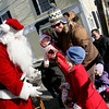 Rockport: Morgan O'Sullivan-Place, 4, looks up at Santa after receiving a bag of fruit and candy with her mom, Erin, and sister Cayla, 1 year, at Dock Square Christmas morning.  <br /> Photo by Mary Muckenhoupt/Gloucester Daily Times Thursday, December 25, 2008