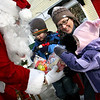 Rockport: Santa hands out bags of fruit and candy to Cole Fung, 3, and his sister Paige, 2, with mom Jaimie at Dock Square Christmas morning.  <br /> Photo by Mary Muckenhoupt/Gloucester Daily Times Thursday, December 25, 2008