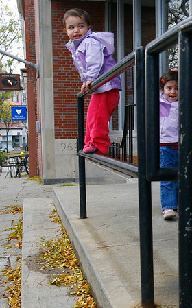 Gloucester: Sarah Fernandes, 19 months, and her sister, Katie Fernandes, 3, play on the railing outside Sovereign Bank on Main Street yesterday afternoon after stopping at Lone Gull with their mom and friends. The railing is one of their favorite places to play in Gloucester. Photo by Kate Glass/Gloucester Daily Times Tuesday, October 28, 2008
