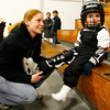 Gloucester: Rheana Bednarik of Gloucester helps her son, Dylan, 4, with his skates at the Talbot Rink during Cape Ann Youth Hockey's family night on Monday. Photo by Kate Glass/Gloucester Daily Times Monday, November 10, 2008