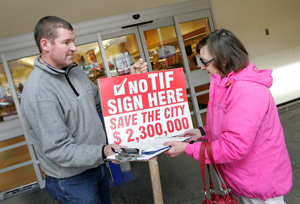 Gloucester: Anne Pothier signs the petition from Jamie O'Hara, left, asking the Gloucester City Council to rescind their vote granting tax increment financing (TIF) to Gloucester Crossings in front of Stop and Shop on Bass Avenue Friday afternoon. The deadline for receiving the needed signatures was yesterday at 5 p.m.  Mary Muckenhoupt/Gloucester Daily Times.