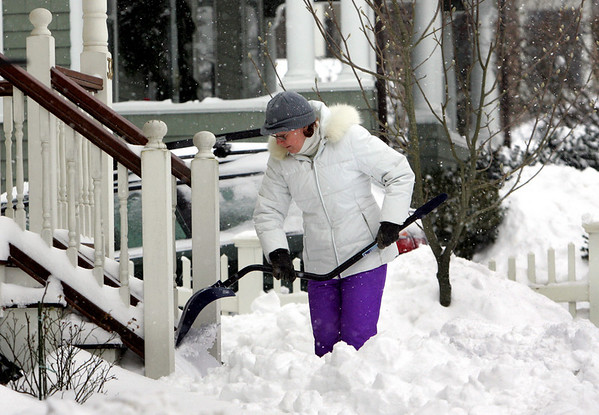 Manchester: Andy Bago cleans off her front porch on Lincoln Street as ocean effect snow continued to fall Saturday morning. Mary Muckenhoupt/Gloucester Daily Times