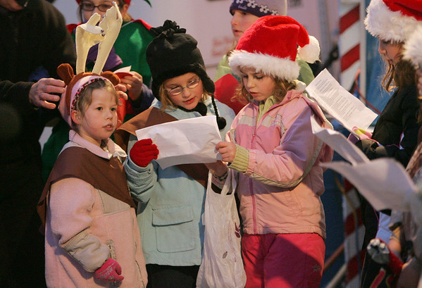 Gloucester: From left, Jesse Alexander, Lilly Herdman and Bailey Marshall, from Brownie troop 22, sing Christmas carols at the tree lighting ceremony at Kent Circle Sunday night. Mary Muckenhoupt/Gloucester Daily Times