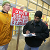 Gloucester: William Hartwell signs the petition from John D. O'Hara, left, asking the Gloucester City Council to rescind their vote granting tax increment financing (TIF) to Gloucester Crossings in front of Shaws on Railroad Avenue Wednesday evening. 2100 signatures are needed by December 24th. Mary Muckenhoupt/Gloucester Daily Times