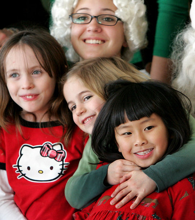 Manchester: From left, Courtney Dellicker, Lydia Shaw, and Emily Schuh, kidergarteners from Manchester Memorial Elementary School, sit with Mrs. Claus at Manchester Essex High School Thursday afternoon.  All kindergarten classes walked over to the high school to meet Santa and tell him what they wanted for Christmas. Mary Muckenhoupt/Gloucester Daily Times