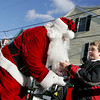 Rockport: Joe Ryan of Rockport receives a bag of fruit and candy from Santa at Dock Square Christmas morning.  <br /> Photo by Mary Muckenhoupt/Gloucester Daily Times Thursday, December 25, 2008