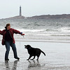 Gloucester: Nell Abercrombie of Gloucester throws her dog Mr. Willdo a tennis ball as her smaller dog Oliver stays by her side at Good Harbor Beach Saturday morning. Mary Muckenhoupt/Gloucester Daily Times