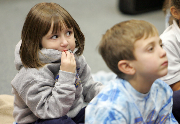 "Gloucester: Cassie Gove, sitting behind Tucker Destino, listens to Charlie Vogel read ""How the Grinch Stole Christmas"" At Sawyer Free Library Thursday morning. The kidergarten class of St. Ann School came down to the library to listen to Vogel read them a story and to sing Christmas carols. Mary Muckenhoupt/Gloucester Daily Times."