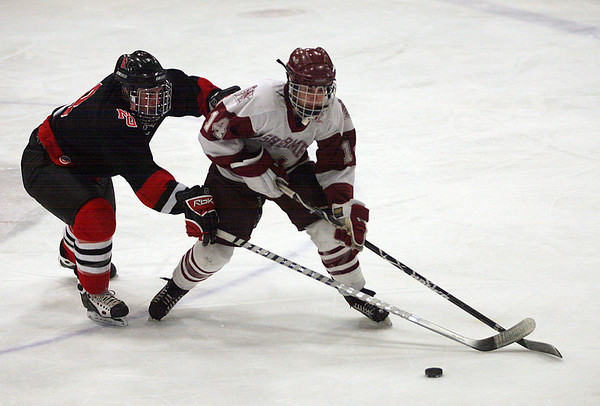 Gloucester: Gloucester's Nick Decoste tries to shield the puck from North Quincy's Matt Rodriguez during the consolation game of the Cape Ann Savings Bank Holiday Tournament last night. Photo by Kate Glass/Gloucester Daily Times Tuesday, December 30, 2008