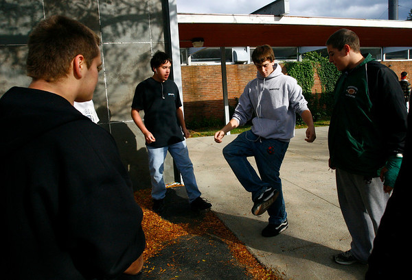 Manchester: Aaron Gray, left, Matt Stevens, and Matt Wescott, right, watch as David Wright, center, kicks the hacky sack around while they wait for football practice to start at Manchester Essex High School yesterday afternoon. Photo by Kate Glass/Gloucester Daily Times Wednesday, October 29, 2008