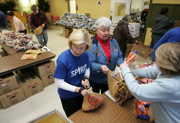 Gloucester: From left, Janet Atkinson, Corinne Holt, and Suzanne Capel pack bags with carrots, squash and gravy packets at the Cape Ann Food Pantry as volunteers works to get turkey meal baskets together for distribution Friday afternoon.  Over 100 turkey meal baskets will also be delivered to neighborhoods in Gloucester and Rockport today.  Mary Muckenhoupt/Gloucester Daily Times