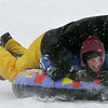 Gloucester: Tim Philpott of Gloucester hitches a ride with his son John, 10,  down a hill at Stage Fort Park while enjoying an afternoon of sledding on freshly fallen snow Saturday. Mary Muckenhoupt/Gloucester Daily Times