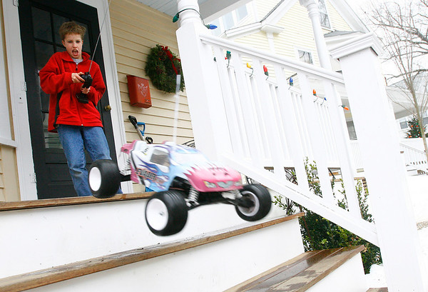 "Manchester: Nick Warren, 11, of Manchester makes his remote-control car leap off his front porch. Warren received the car as a Christmas gift and says he really likes making it do 360s and jumps. ""It's a good thing it has good shocks,"" he says.<br /> Photo by Kate Glass/Gloucester Daily Times Sunday, December 28, 2008"