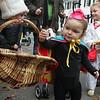 Manchester: Vienna Wyler, 18 months, takes abox of Junior Mints while wlalking the Wobblin' Goblin parade with her sister Amelia, 3, right, and her parents Saturday morning. Children paraded through town from Town Hall to the Community Center gathering treats along the way. Mary Muckenhoupt/Gloucester Daily Times