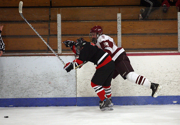 Gloucester: Gloucester's Dylan Morrissey tries to knock North Quincy's Paul Reardon away from the puck during the consolation game of the Cape Ann Savings Bank Holiday Tournament last night. Photo by Kate Glass/Gloucester Daily Times Tuesday, December 30, 2008