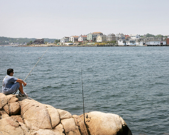 Gloucester:  Joe Ciaramitaro, of Gloucester, fishes from the rocks by the Paint Factory for striped bass, overlooking the view of the Fort neighborhood across the inner harbor on Thursday afternoon.  The Fort neighborhood is being eyed for a complete rezoning as part of a Gloucester Harbor revitalization plan.   <br /> Photo by Kristen Olson/Gloucester Daily Times Thursday, July 03, 2008