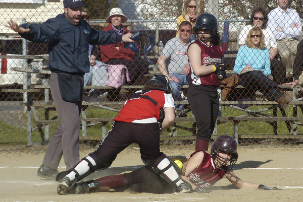 Gloucester: Gloucester High School's Kelly Benson slides safely under the tag of Marblehead catcher Lizzy Whitehill Friday at Burnham's Field. Benson stole home after the catcher threw the pitch back to the pitcher in the bottom of the fourth inning. Behind is Gloucester captain Olivia Frontiero who was at bat at the time. Gloucester lost 8-6.<br /> Photo by Mike Dean/Gloucester Daily Times Friday, April 18, 2008