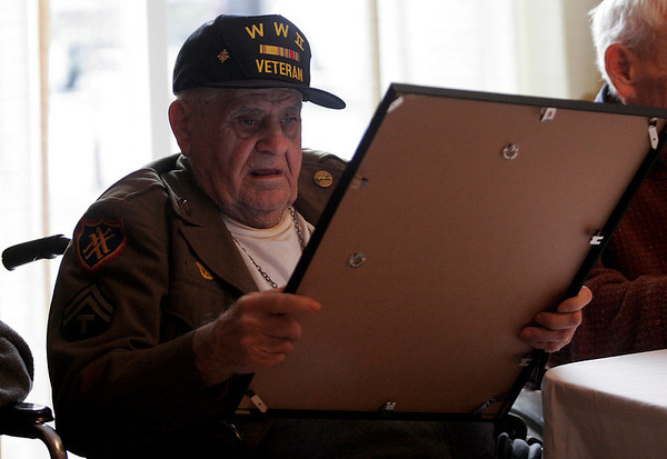 Gloucester: Louis Krupanski, wearing his World War II jacket, looks at a plaque thanking him for his service during a Veterans Day ceremony at Golden Living yesterday. Photo by Kate Glass/Gloucester Daily Times Tuesday, November 11, 2008