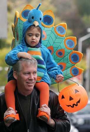 Manchester: Emma Hawthorne, 3, rides on the shoulders of her dad, Dan, during the Wobblin' Goblin Parade in Manchester Saturday morning. The parade began at Town Hall and ended at the Community Center and children gathered candy from shop owners along the way. Mary Muckenhoupt/Gloucester Daily Times