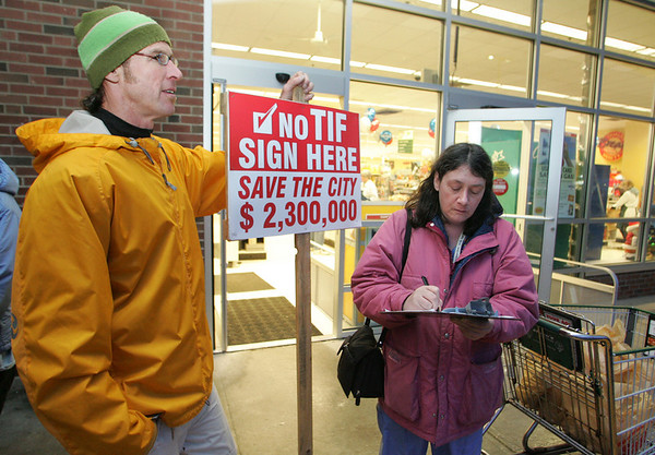 Gloucester: Joan Luoni signs the petition from John D. O'Hara, left, asking the Gloucester City Council to rescind their vote granting tax increment financing (TIF) to Gloucester Crossings in front of Shaws on Railroad Avenue Wednesday evening. 2100 signatures are needed by December 24th. Mary Muckenhoupt/Gloucester Daily Times