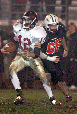Gloucester: Gloucester's Taylor Burbine runs with the ball as Salem's Frank Vieira stays in close pursuit during the Gloucester vs. Salem football game held at Bertram Field Friday night. Mary Muckenhoupt/Gloucester Daily Times.