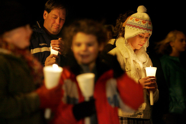 Essex: Alexandra Marshall, 11, of Essex looks down at her candle during the memory tree lighting in front of Essex Town Hall Thursday evening.  Alexandra was there to hang an ornaments in memory of Betty Ann Crossen and her grandfather Andy Marshall. Mary Muckenhoupt/Gloucester Daily Times