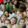 Manchester: Lea Sutherland, center, sits among hundreds of students who filled the gymnasium at Manchester Memorial Elementary School for the school's holiday concert Friday morning. Mary Muckenhoupt/Gloucester Daily Times