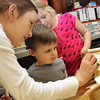 Manchester: Sebron Rowe, 3, of Manchester gets some help from his neighbors Haley New, 8, and her sister Lexi, 10, front, to finish making his birdhouse at the Manchester Public Library during winter crafts Thursday afternoon.  Mary Muckenhoupt/Gloucester Daily Times